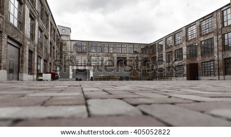 Ground level view from brick paving stones of old warehouse exterior with large windows and dock doors under gray cloudy sky #405052822