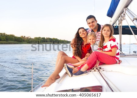 Beautiful happy family with two daughters having great time at the yacht at summertime. Travel and vacation concept #405065617