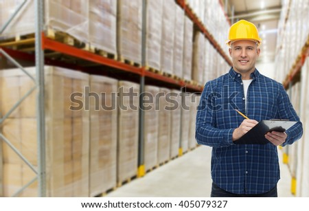 wholesale, logistic, business, export and people concept - happy man or manager in helmet with clipboard and pencil checking goods over warehouse background #405079327