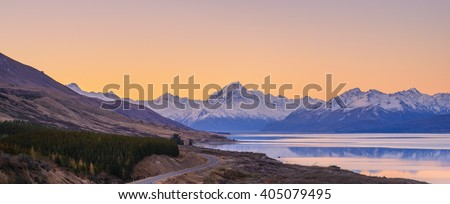 Scenic view at Peters Lookout, Mount Cook Road alongside Lake Pukaki with snow capped Southern Alps basking in the late winter afternoon light. The setting sun cast beautiful vivid hues on the sky. #405079495