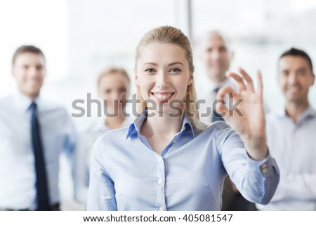 business, people, gesture and teamwork concept - smiling businesswoman showing ok sign with group of businesspeople in office #405081547