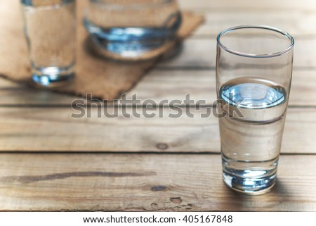 Glass of water on a wooden table. Selective focus. Shallow DOF #405167848