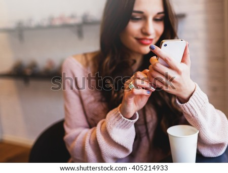 Woman typing write  message on smart phone in a  modern cafe. Cropped image of young  pretty girl sitting at a table with  coffee or cappuccino  using mobile phone. Royalty-Free Stock Photo #405214933