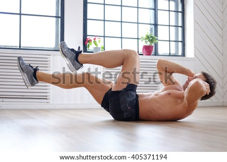 Shirtless muscular man doing stomach workouts lying on a floor. #405371194