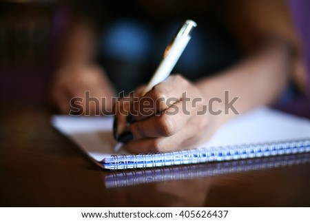 African woman writing in notebook.  Focus on hands.  #405626437