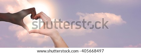 Black and white hand forming a heart in front of a blue sky #405668497