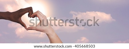 Black and white hand forming a heart in front of a blue sky #405668503