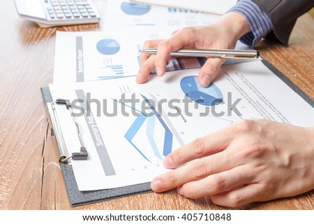 business man analyzing graph and chart document report, business performance concept #405710848