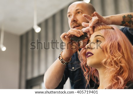 Beautiful woman getting haircut by hairdresser in the beauty salon. Royalty-Free Stock Photo #405719401