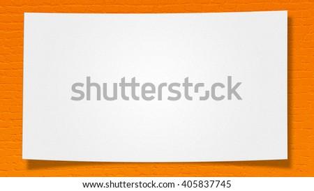 White paper on orange brick wall