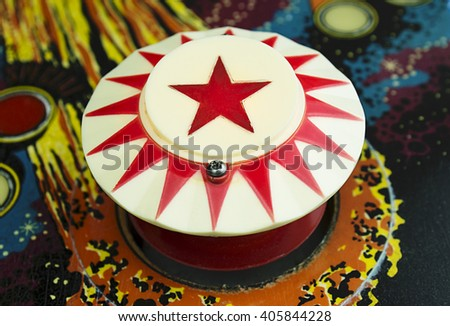 A Bumper with a red star on a Pinball Machine Royalty-Free Stock Photo #405844228