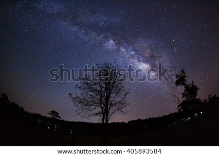 Beautiful milky way galaxy on a night sky and silhouette of tree with cloud, Long exposure photograph.with grain #405893584