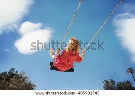 Little girl having fun on a swing outdoor #405901945