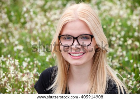 Blonde girl with glasses in the field surrounded by flowers #405914908