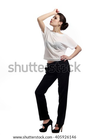 close-up portrait of young brunette in business style,  in white blouse and black trousers on the  light background studio #405926146