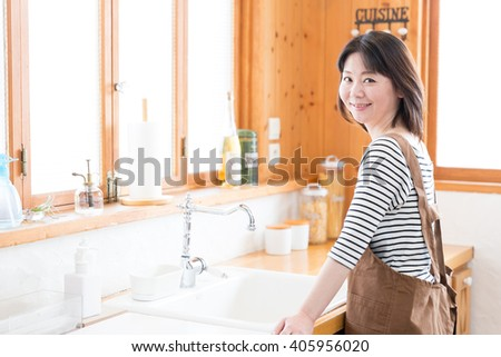 portrait of asian woman relaxing in the kitchen  #405956020