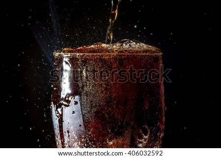 Soda large glass, overflowing glass of soda closeup with bubbles isolated on black background #406032592