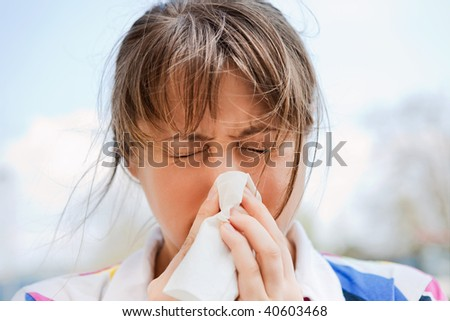 Young blonde female blowing her nose #40603468