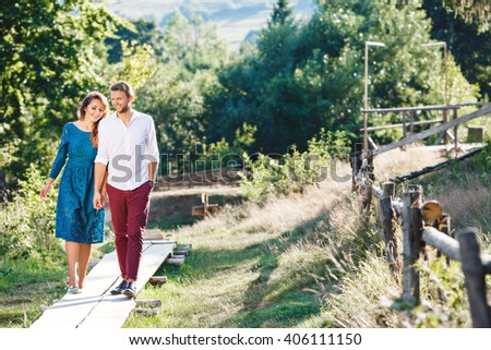 Nice couple walking together, outdoor, in the countryside. Beloved holding hands of each other and smiling. Girl looking down and man looking straight. Full body #406111150