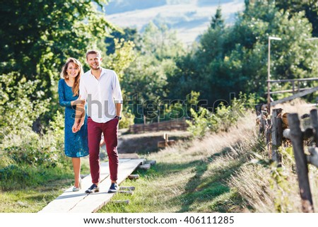 Nice couple standing together, outdoor, in the countryside. Woman wearing blue dress and light blue shoes and man wearing white shirt, claret trousers and black shoes. Girl holding man's hand. #406111285