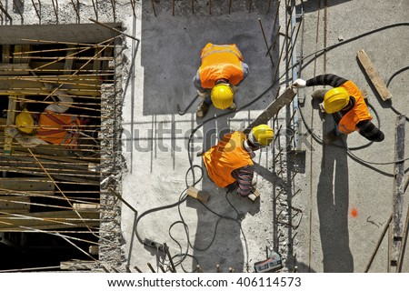 Construction site workers - aerial - Top View Royalty-Free Stock Photo #406114573