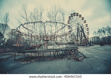 Abandoned carousel and abandoned ferris  at an amusement park in the center of the city of Pripyat, the Chernobyl disaster, the exclusion zone, a ghost town #406461565