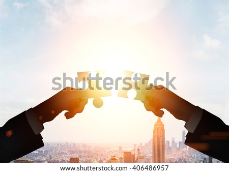 Teamwork concept with businessmen putting puzzle pieces together on cityscape background with sunlight  #406486957