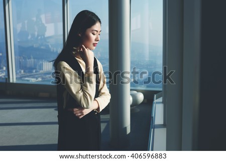 Young Asian woman skilled entrepreneur is looking on a city view from the last floor the tall modern building, while is waiting meeting with international partners during her business trip to New York Royalty-Free Stock Photo #406596883