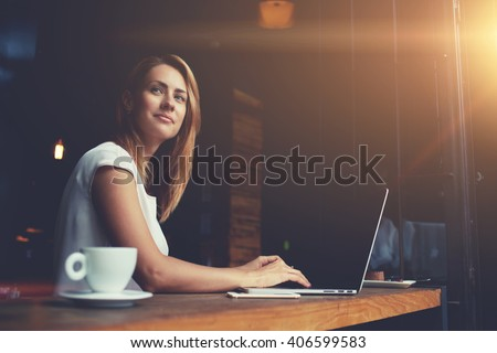 Beautiful Caucasian woman dreaming about something while sitting with portable net-book in modern cafe bar, young charming female freelancer thinking about new ideas during work on laptop computer   #406599583