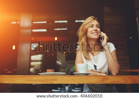 Young charming woman calling with cell telephone while sitting alone in coffee shop during free time, attractive female with cute smile having talking conversation with mobile phone while rest in cafe #406602010