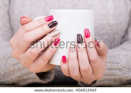 Manicure - Beauty treatment photo of nice manicured woman fingernails holding a cup. Very nice feminine nail art with nice pink,black and gold nail polish. Processed in retro colors. Selective focus. #406812469