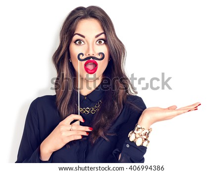 Surprised model Girl holding funny mustache on stick and showing empty copy space on open hand palm for text, white background. Happy girl presenting point. Proposing product. Advertisement gesture #406994386