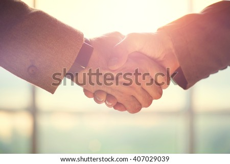 Business handshake. Business handshake and business people concept. Two men shaking hands over sunny office background. Partnership, Deal Royalty-Free Stock Photo #407029039