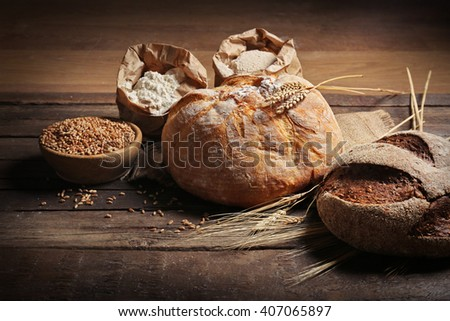 Fresh baked bread, flour and wheat on the wooden background #407065897