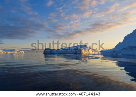 Nature and landscapes of Greenland. Travel on the scientific vessel among ices. Studying of a phenomenon of global warming. Ices and icebergs of unusual forms and colors. #407144143