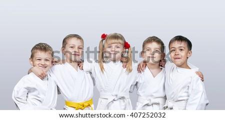Cheerful children in karategi on a gray background #407252032