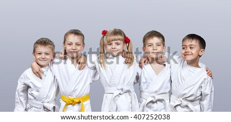 On a gray background little athletes in karategi #407252038