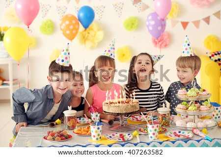 Happy group of children having fun at birthday party Royalty-Free Stock Photo #407263582