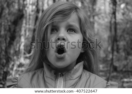 black and white portrait of a little girl in the woods #407522647