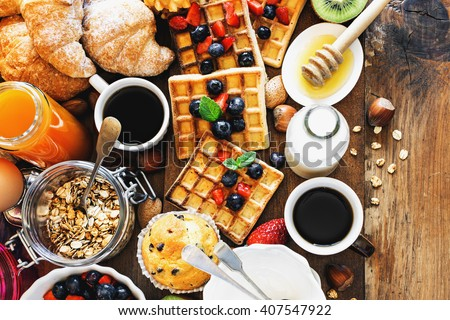 Health and colorful breakfast - cups of coffee with homemade granola, waffles, muffins,almond,hazelnuts,various fresh fruits, berries and milk on old wooden table. Health food concept  .Top view. #407547922