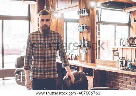 Confident barber expert. Young bearded man looking at camera and keeping hand on chair while standing at barbershop #407606761