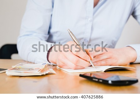 A female accountant at work - writing notes on a paper notebook. #407625886