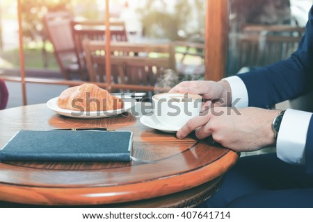 Close-up image of coffee break with a cap of coffee and croissant. Businessman in a jacket sits at the table at office. Good Morning. Cafe, restaurant