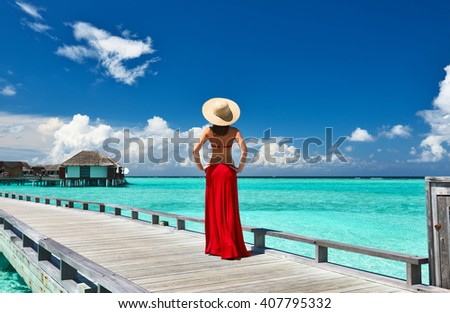 Woman on a tropical beach jetty at Maldives #407795332