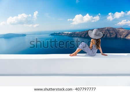 Europe Greece Santorini travel vacation. Woman looking at view on famous travel destination. Elegant young lady living fancy jetset lifestyle wearing dress on holidays. Amazing view of sea and Caldera Royalty-Free Stock Photo #407797777