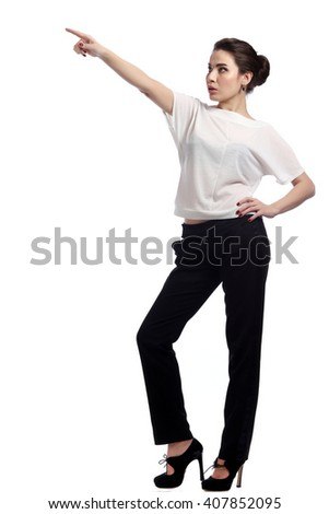 close-up portrait of young brunette in business style,  in white blouse and black trousers on the  light background studio #407852095