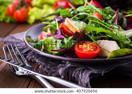 Fresh salad with chicken, tomatoes and mixed greens (arugula, mesclun, mache) on wooden background close up. Healthy food. #407920696