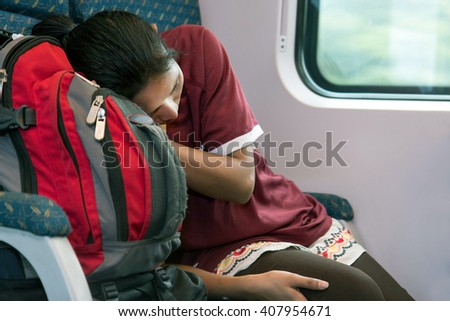 woman with a backpack sleeping in a train #407954671