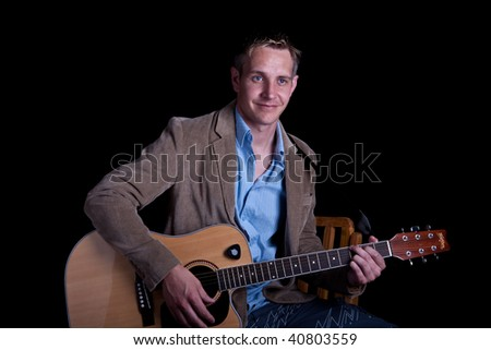 Young Male Guitarist with guitar on his lap playing on black background #40803559