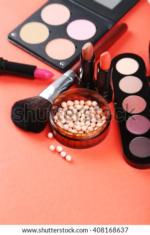 Makeup brush and cosmetics on a red background #408168637